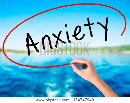 Woman Hand Writing Anxiety With A Marker Over Transparent Board