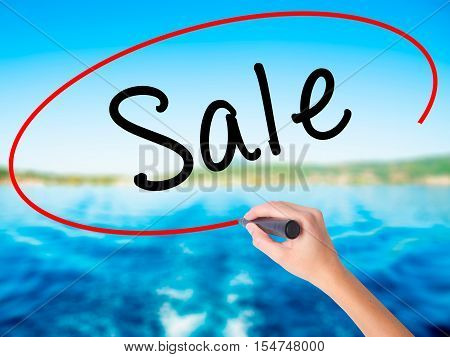 Woman Hand Writing Sale With A Marker Over Transparent Board