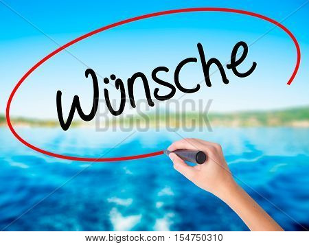 Woman Hand Writing Wunsche (wishes In German) With A Marker Over Transparent Board