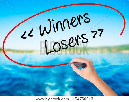 Woman Hand Writing Winners - Losers  With A Marker Over Transparent Board