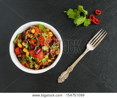 Chili con carne in a white ceramic bowl on black stone background. Cooked with ground beef tomatoes peppers beans corn garlic onion cilantro. Top view.