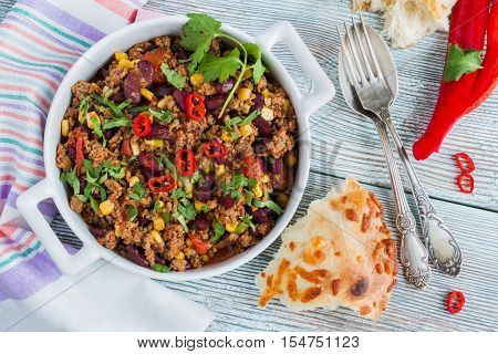 Chili con carne in a white casserole on wooden table with fresh vegetables and bread. Cooked with ground beef tomatoes peppers beans corn garlic onion cilantro. Top view.