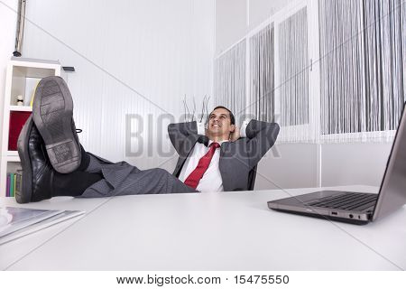 businessman relaxing at the office with his shoes on the desk (isolated on white)