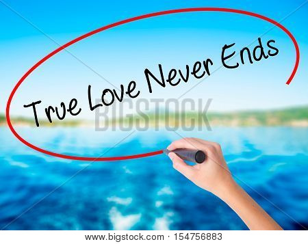 Woman Hand Writing True Love Never Ends With A Marker Over Transparent Board