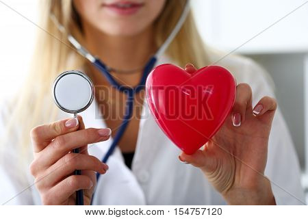 Female medicine doctor hold in hands red toy heart and stethoscope. Cardio therapeutist student education physician make cardiac physical heart rate measure arrhythmia concept