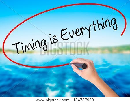 Woman Hand Writing Timing Is Everything With A Marker Over Transparent Board