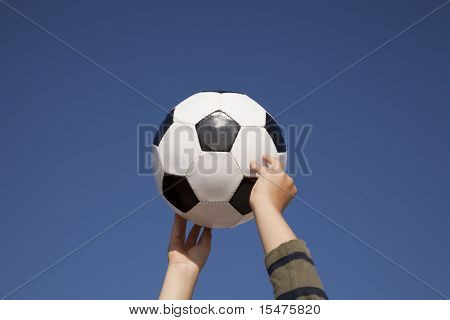 Hands holding a soccer ball up to the sky