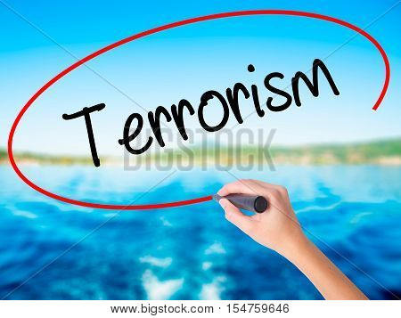 Woman Hand Writing Terrorism With A Marker Over Transparent Board