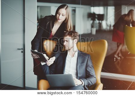 Businesswoman in red dress and jacket showing information on screen of her tablet to her boss on yellow armchair in formal suit with white laptop luxury office