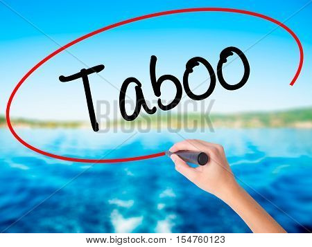 Woman Hand Writing Taboo With A Marker Over Transparent Board