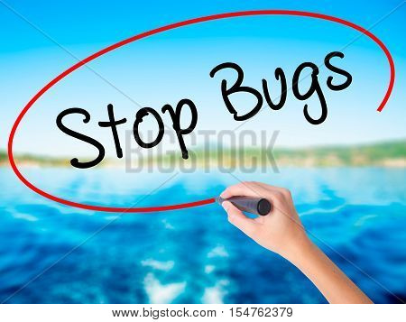 Woman Hand Writing Stop Bugs With A Marker Over Transparent Board