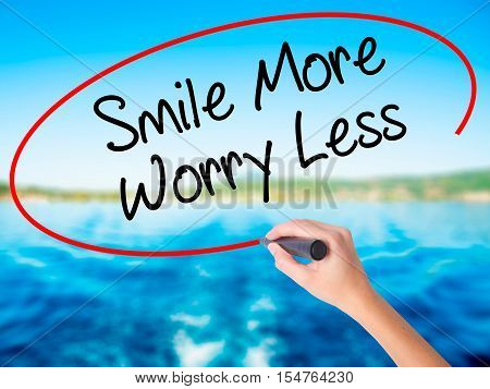 Woman Hand Writing Smile More Worry Less With A Marker Over Transparent Board