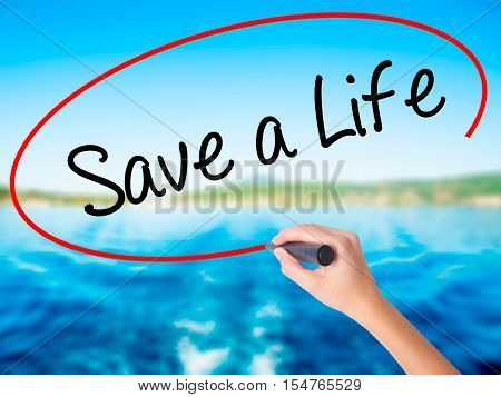 Woman Hand Writing Save A Life  With A Marker Over Transparent Board