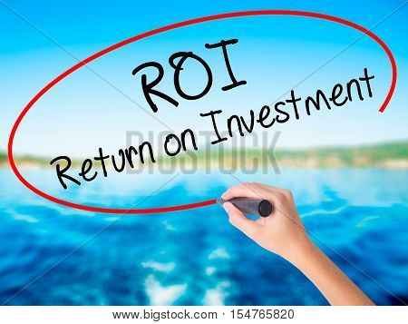 Woman Hand Writing Roi  Return On Investment With A Marker Over Transparent Board