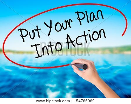 Woman Hand Writing Put Your Plan Into Action With A Marker Over Transparent Board