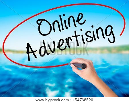 Woman Hand Writing Online Advertising With A Marker Over Transparent Board