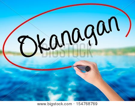 Woman Hand Writing  Okanagan With A Marker Over Transparent Board