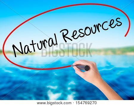 Woman Hand Writing Natural Resources With A Marker Over Transparent Board