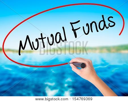 Woman Hand Writing Mutual Funds  With A Marker Over Transparent Board
