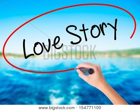 Woman Hand Writing Love Story With A Marker Over Transparent Board
