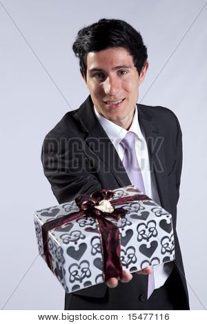 Businessman offering you a christmas gift (isolated on gray)