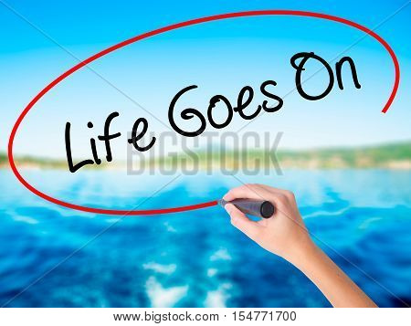 Woman Hand Writing Life Goes On With A Marker Over Transparent Board