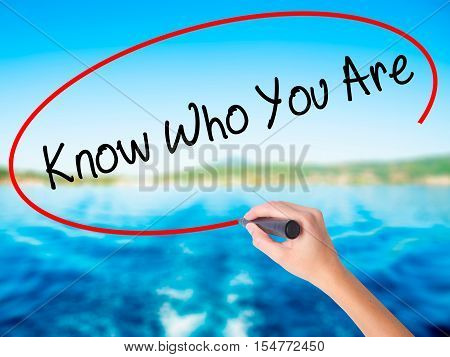 Woman Hand Writing Know Who You Are With A Marker Over Transparent Board
