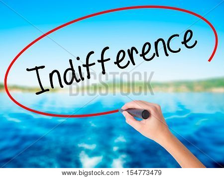 Woman Hand Writing Indifference  With A Marker Over Transparent Board