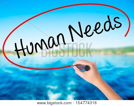 Woman Hand Writing Human Needs With A Marker Over Transparent Board.