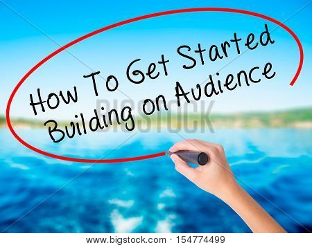 Woman Hand Writing How To Get Started Building On Audience With A Marker Over Transparent Board