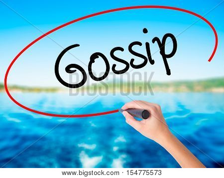 Woman Hand Writing Gossip With A Marker Over Transparent Board