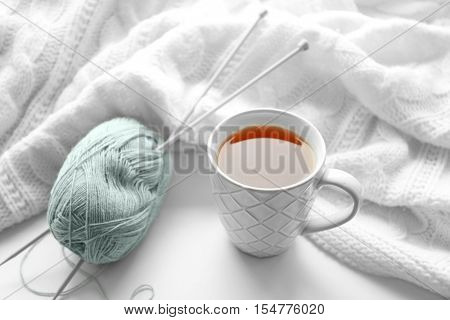 Hot drink with threads and plaid on windowsill