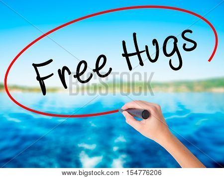 Woman Hand Writing Free Hugs With A Marker Over Transparent Board