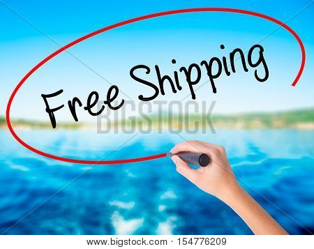 Woman Hand Writing Free Shipping With A Marker Over Transparent Board
