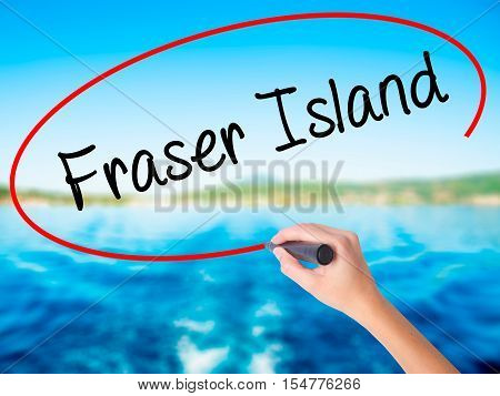 Woman Hand Writing Fraser Island With A Marker Over Transparent Board.