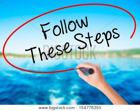 Woman Hand Writing Follow These Steps With A Marker Over Transparent Board