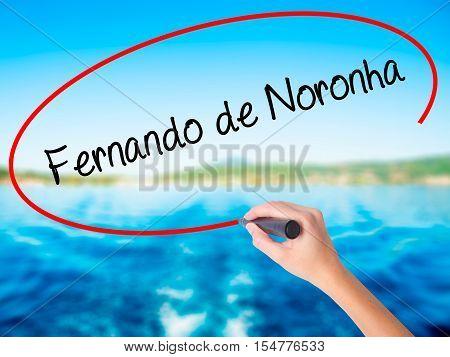 Woman Hand Writing Fernando De Noronha With A Marker Over Transparent Board