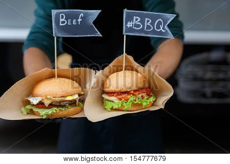 Fresh beef burgers cooked at barbecue outdoors. Cookout american bbq food with text labels. Big hamburgers with steaks meat and vegetables closeup with chef unfocused at background. Street fast food.