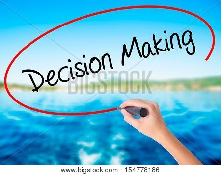 Woman Hand Writing Decision Making With A Marker Over Transparent Board