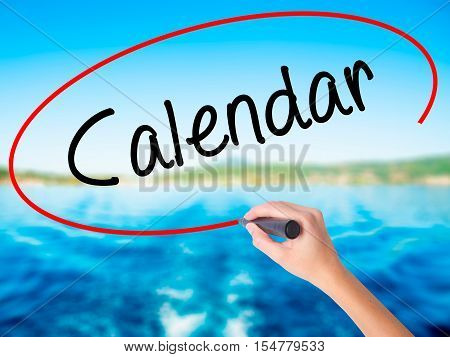 Woman Hand Writing Calendar   With A Marker Over Transparent Board