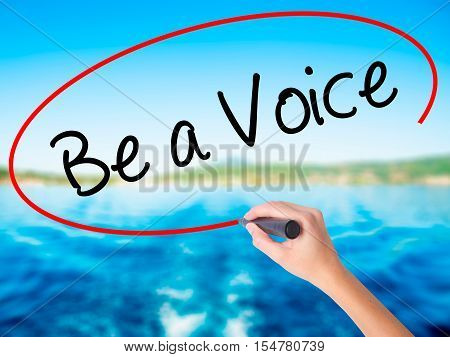 Woman Hand Writing Be A Voice With A Marker Over Transparent Board