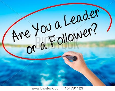 Woman Hand Writing Are You A Leader Or A Follower? With A Marker Over Transparent Board