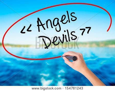Woman Hand Writing Angels - Devils With A Marker Over Transparent Board.