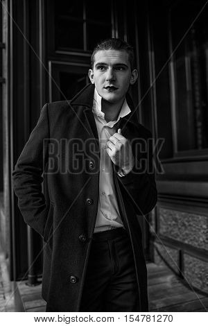 a handsome man in a black coat and white shirt