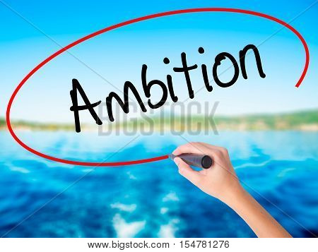Woman Hand Writing Ambition With A Marker Over Transparent Board