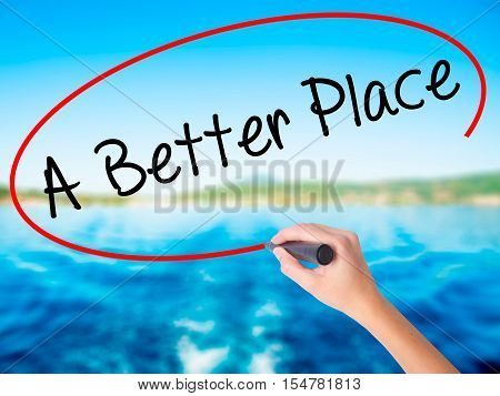 Woman Hand Writing A Better Place With A Marker Over Transparent Board