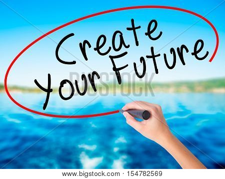 Woman Hand Writing Create Your Future With A Marker Over Transparent Board