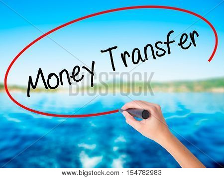 Woman Hand Writing Money Transfer  With A Marker Over Transparent Board