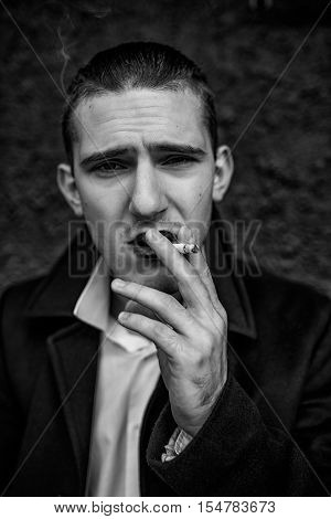 brutal sexy young guy smoking a cigarette