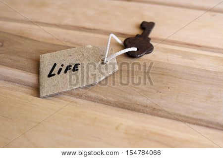 The concept of a happy life - the old key with a tag on wooden background.